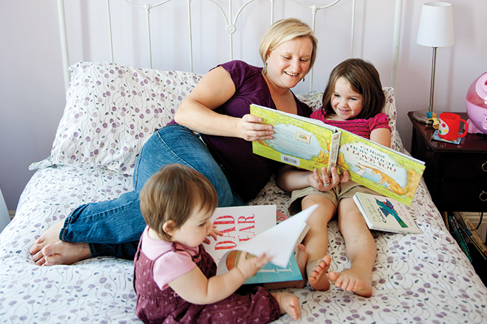 Researcher Elizabeth Pufall Jones '98 enjoys book time with Ella, 1, and Haley, 4.